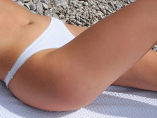 A closeup view of a woman's lower half lying on her back with her leg raised.