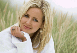 A blonde woman with medium length hair posing in some long reeds.