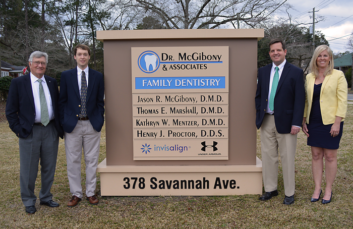 Dr. McGibony and his associates stand by the business sign.