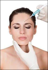 A woman with her eyes closed with two gloved hands preparing to inject a syringe into her facial skin.