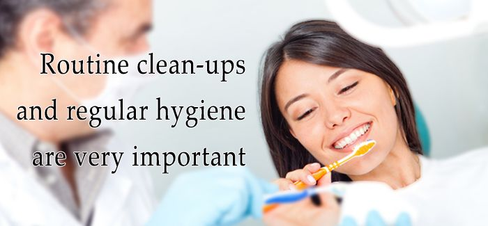 "A photograph of a woman with a dentist with the text ""Routine clean-ups and regular hygiene are very important"" in the foreground."