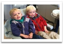 Two young blond boys in dental exam chair