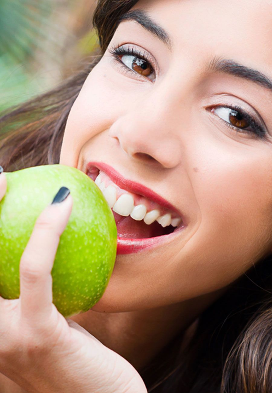 Young smiling woman holding a green apple