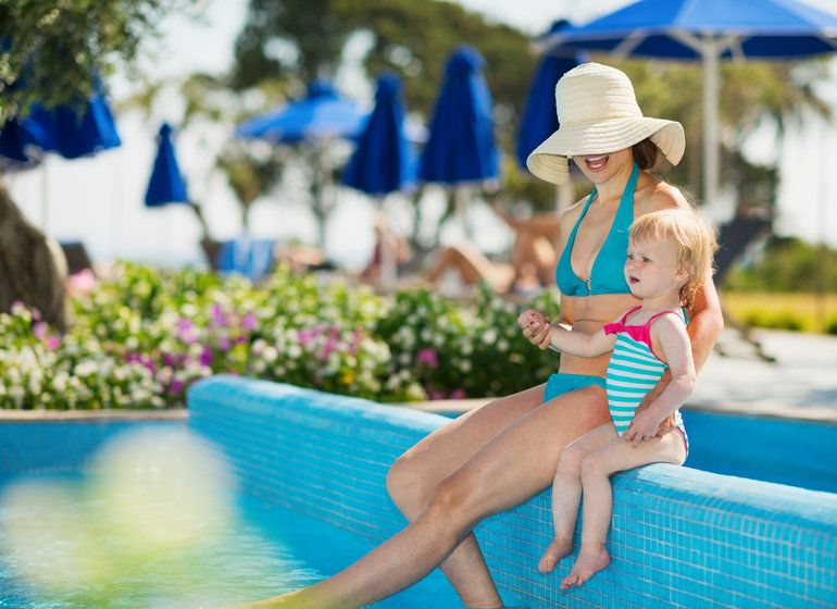 A mother sits by the pool with her young daughter at a vacation resort