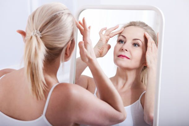Woman rubbing temples while looking in a mirror