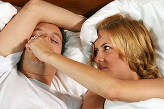 A woman trying to keep her partner from snoring