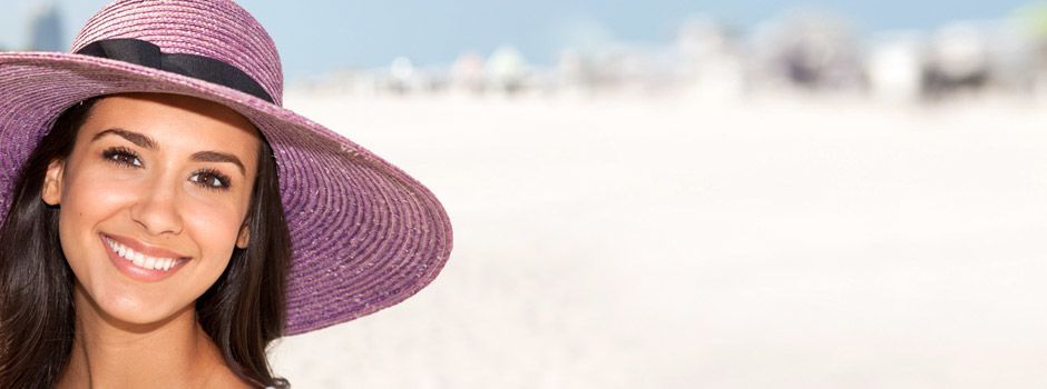A woman in a purple hat by the beach
