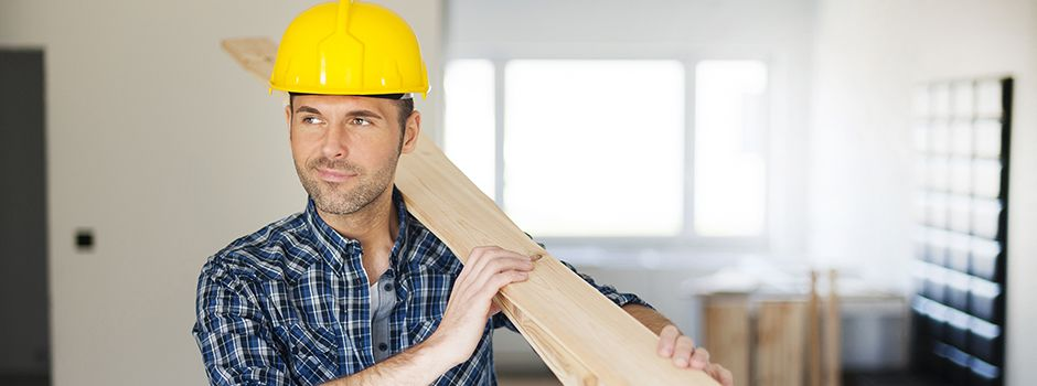 A construction worker carrying wood