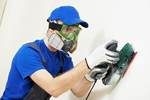 A worker wearing a respirator while sanding a wall