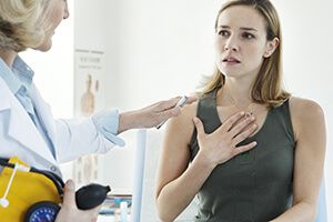 A woman touching her chest as a doctor looks on