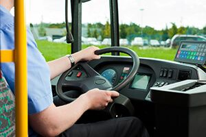 A bus driver's hands on the steering wheel