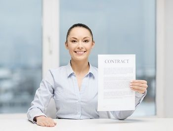 Seated woman in business attire holds up