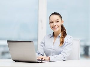 Smiling, professionally-attired young woman sits before laptop computer