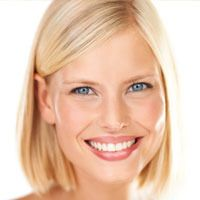 Blonde female with blue eyes smiles following a cosmetic dentistry appointment