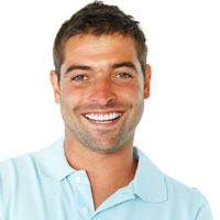 Attractive male wearing a blue shirt smiles following his smile makeover