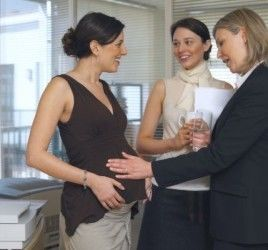 Two women discuss surrogacy with a pregnant mother.