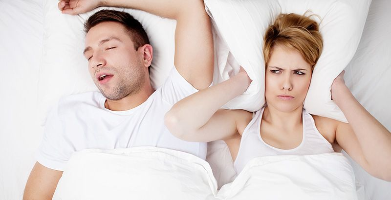 A frustrated woman holds her pillow to her ears to shield the sound of her bedmate's snoring.