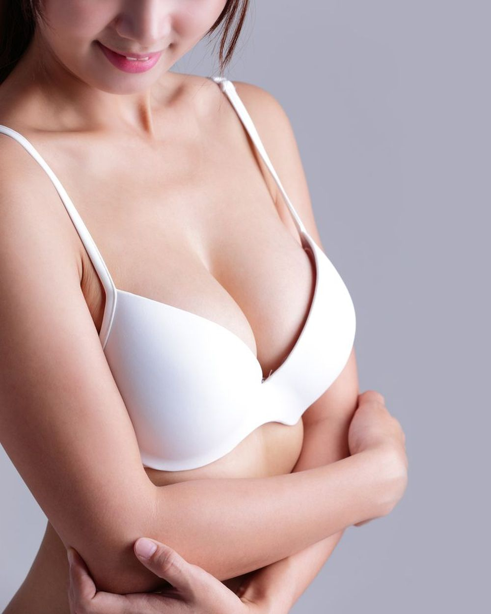 A woman in a white bra with implants