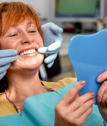 Smiling dental implant patient holding mirror in her hands