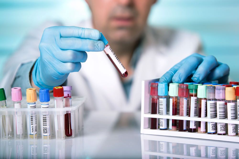 A medical professional holds a vial of blood