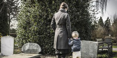 Woman and young boy looking at a grave stone