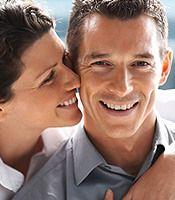 Smiling woman whispering in man's ear