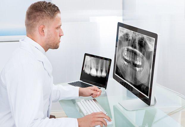 Man looking at dental x-rays on monitor