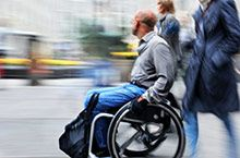A man riding a wheelchair down the street