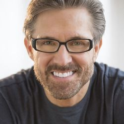 Smiling middle-aged man in gray shirt and glasses