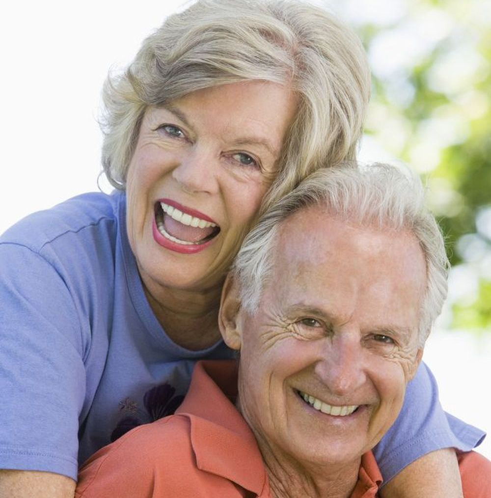 An older couple is happy after getting new dentures at a great price