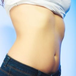 A woman's shirt is raised to expose her slim stomach