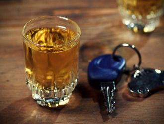 A shot glass of liquor beside car keys