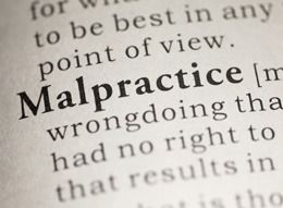 Close-up of the word 'malpractice' on a dictionary page