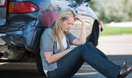 A distraught woman sitting by her car after a crash