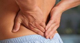 A man holding his lower back in pain