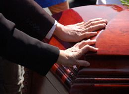 Hands touching a casket