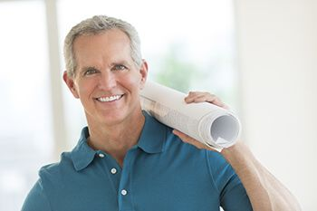 Smiling grey-haired man with a roll of papers