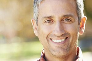 Grey-haired man smiling outdoors
