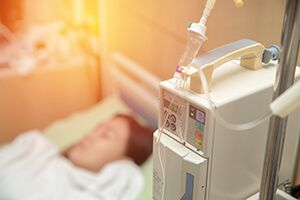 An IV machine in the foreground with a patient lying in bed in the background
