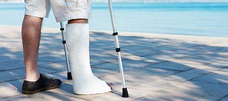 Man with crutches and cast next to pool