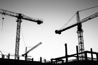 A black and white photo of two construction cranes