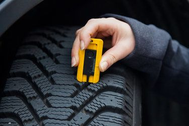 A woman's hand using a tool to check the tread on a vehicle tire