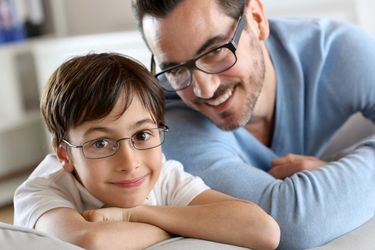 Smiling father and son wearing glasses