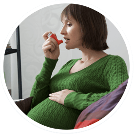 Pregnant woman breathing from an inhaler