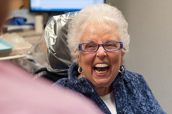 Older woman laughing in dentist's chair