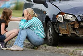 Distraught woman sitting beside a car after an accident
