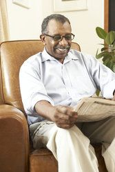 Elderly black man reading the newspaper with glasses