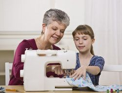 A grandmother helping her granddaughter learn how to sew