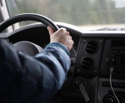 Back view of man holding the steering wheel of a vehicle