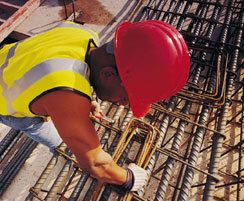 Worker in hard hat performs task from elevated height